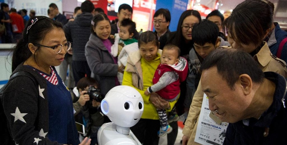 "In this Friday, Oct. 21, 2016 photo, visitors crowd around Pepper, a companion robot from e-commerce giant Alibaba, during the World Robot Conference in Beijing. China is showcasing its burgeoning robot industry as it seeks to promote use of more advanced technologies in Chinese factories and create high-end products that redefine the meaning of ""Made in China."" China will have to make big strides to leap ahead of Germany, Japan and other nations whose robots are generations ahead. (AP Photo/Ng Han Guan)"