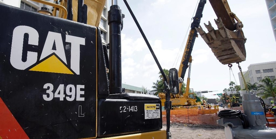 FILE - In this Wednesday, Sept. 17, 2014, file photo, a Caterpillar 349E Hydraulic Excavator operates on a construction site in Miami Beach, Fla. Caterpillar reports financial results Tuesday, Oct. 25, 2016. (AP Photo/Wilfredo Lee, File)