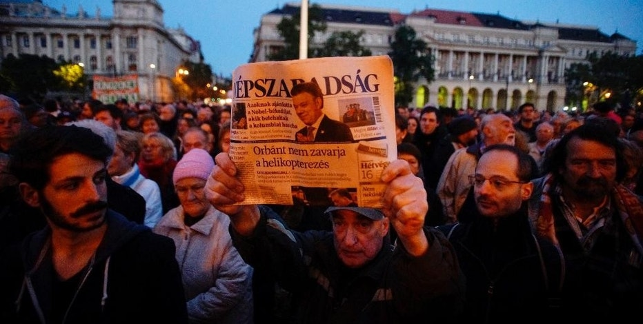 FILE - In this Oct. 8, 2016 file picture a man  shows the last printed edition of Nepszabadsag during a demonstration organized to express solidarity with Hungarian political daily Nepszabadsag in Budapest, Hungary. Earlier in the day the publishing company Mediaworks suspended the publication of both the print and online editions of the paper until it comes up with a new business model. A company linked to an ally of Hungary's prime minister says it has bought the company that publishes the main opposition newspaper, which suspended publication weeks ago. The deal, announced Tuesday Oct. 25, 2016  by the Budapest Stock Exchange, seems to confirm concerns that the sale of Mediaworks, publisher of the leftist Nepszabadsag and many other newspapers and magazines, will further increase government influence over Hungarian media and diminish press diversity.  (Zoltan Balogh/MTI via AP.File )