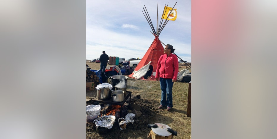 Mary Young Bear, of Tama, Iowa, cooks buffalo and potatoes over a campfire Monday, Oct. 24, 2016, at the Dakota Access oil pipeline protest in southern North Dakota. The long-running dispute over the Dakota Access oil pipeline expanded to private land recently purchased by the pipeline builders, with protesters who say the area rightfully belongs to Native Americans setting up camp and vowing to stay put until the project is stopped.  (AP Photo/Blake Nicholson)