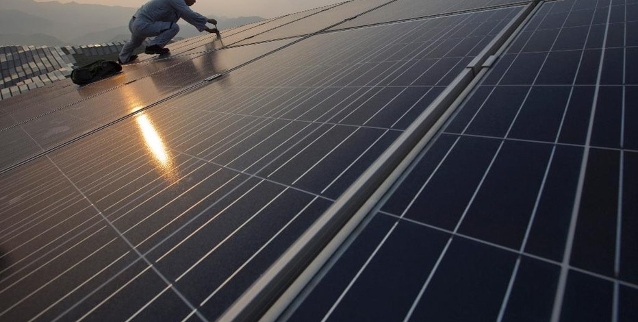 In this Aug. 21, 2016 photo, a worker performs maintenance work on solar panels at a photovoltaic power station in Songxi county in southeast China's Fujian province. Solar panels are among a series of industries from steel and cement to wind turbines in which Chinese production capacity soared during the past decade's economic boom until it vastly exceeded demand. (Chinatopix via AP)