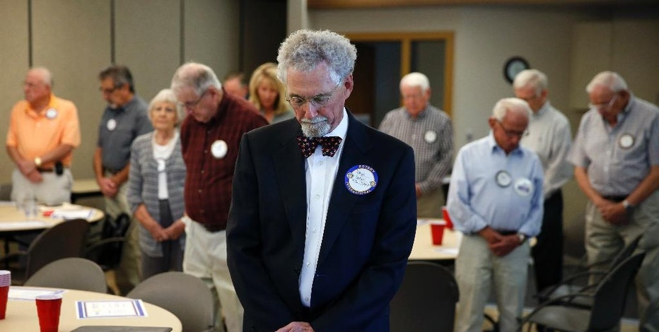 In this Monday, Oct. 24, 2016, photo, Ralph Ogden, a lawyer and advocate for Colorado Amendment 69, bows during an invocation at a Rotary Club luncheon in Wheat Ridge, Colo. Ogden spoke to the group in favor of Amendment 69, which he helped write, and which would repeal the current health insurance system and make coverage universal. (AP Photo/Brennan Linsley)