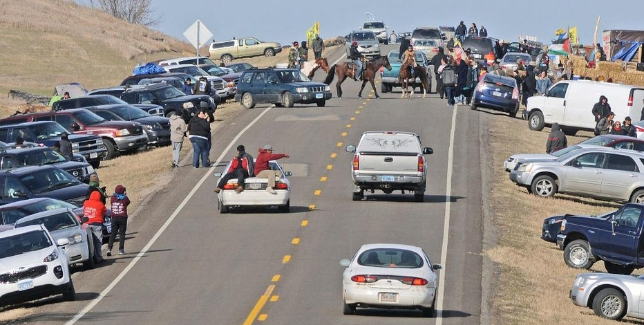 People protesting the Dakota Access Pipeline gather along North Dakota Highway 1806 in Morton County at the site of a new camp that was being put together on Monday, Oct. 24, 2016, in Cannonball, N.D. On Sunday a road block made from rocks, wood and hay bales was put in place but later taken down. The protesters erected tents and teepees on the property along the pipeline route over the weekend. (Tom Stromme/The Bismarck Tribune via AP)