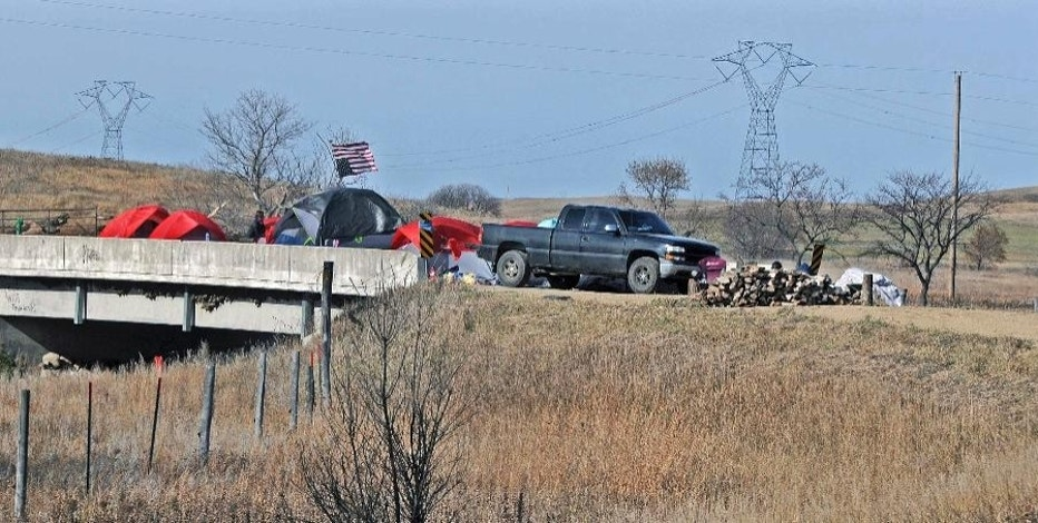 A bridge over the Cannonball River was blocked and barricaded shutting down Morton County Road 134 to any motor vehicle traffic on Monday, Oct. 24, 2016, in Cannon Ball, N.D. People at the site refused to answer a reporters questions. Protesters erected tents and teepees on the property along the Dakota Access oil pipeline route over the weekend. The local sheriff's office called it trespassing, but said it wouldn't immediately remove the more than 100 people because it didn't have the manpower. (Tom Stromme/The Bismarck Tribune via AP)