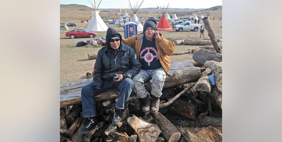 Loren Bagola, 45, left, and Camille Bagola, 27, of Eagle Butte, S.D., who have been living at the Sacred Stones Overflow Camp in Morton County, visit the new camp being put up on the route of the Dakota Access oil pipeline, Monday, Oct. 24, 2016, in Cannon Ball, N.D. The protesters erected tents and teepees on the property along the pipeline route over the weekend. The local sheriff's office called it trespassing, but said it wouldn't immediately remove the more than 100 people because it didn't have the manpower. (Tom Stromme/The Bismarck Tribune via AP)