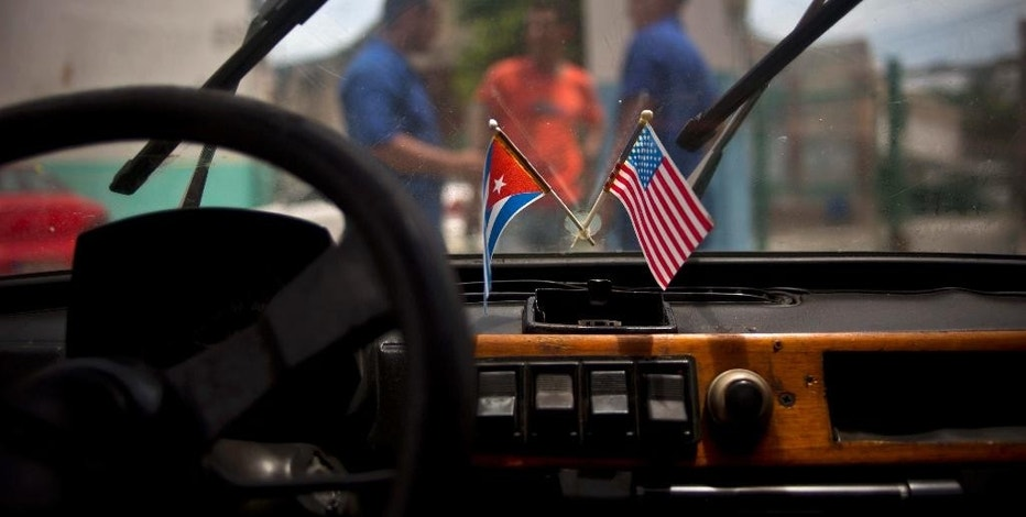 FILE - In this Aug. 10, 2016 file photo a Cuban and a U.S. flag hang on the windshield of a car in a garage in Havana, Cuba. Diplomats say the U.S. is expected to abstain, for the first time, from a U.N. resolution criticizing America's economic embargo against Cuba. Such a step would effectively pit the Obama administration, with the UN, against the Republican-led Congress, which supports the 55-year-old embargo despite the United States' resumption of full diplomatic relations with Cuba.  (AP Photo/Ramon Espinosa, File)