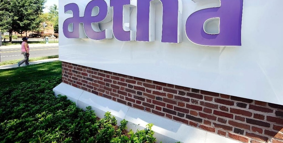 FILE - In this Tuesday, Aug. 19, 2014, file photo, a pedestrian walks past a sign for Aetna Inc., at the company headquarters in Hartford, Conn. Aetna reports financial results Thursday, Oct. 27, 2016. (AP Photo/Jessica Hill, File)