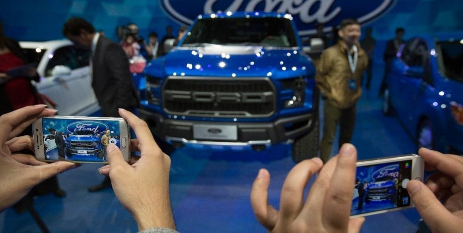FILE - In this April 23, 2016, file photo, attendees take photos of a Ford F-150 Raptor pickup truck by smartphones at a promotional event for Ford ahead of the biennial Auto China car show in Beijing. Ford Motor Co. reports financial results Thursday, Oct. 27, 2016. (AP Photo/Mark Schiefelbein, File)