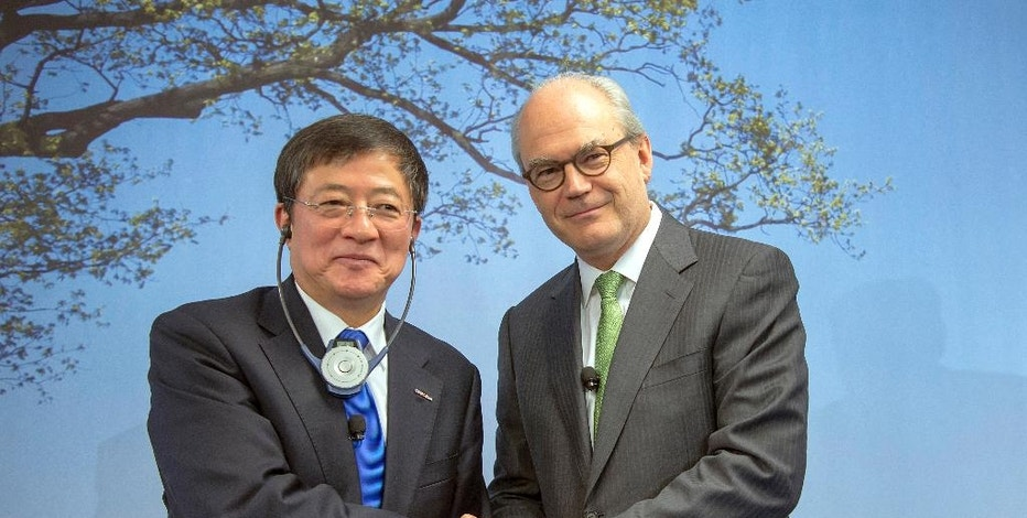 """FILE - In this Feb. 3, 2016, file photo, Ren Jianxin, left, chairman of ChemChina (China National Chemical Corporation), and Michel Demare, chairman of the Board of Directors of Syngenta, pose for a photo after an annual press conference of agrochemical company Syngenta in Basel, Switzerland.  Swiss chemical giant Syngenta said Tuesday, Oct. 25, 2016,  that EU regulators tasked with examining its proposed $43 billion takeover by state-owned ChemChina have """"recently requested a large amount of additional information,"""" which will drag the approval process out into the first quarter of next year. (Georgios Kefalas/Keystone via AP, File)"""