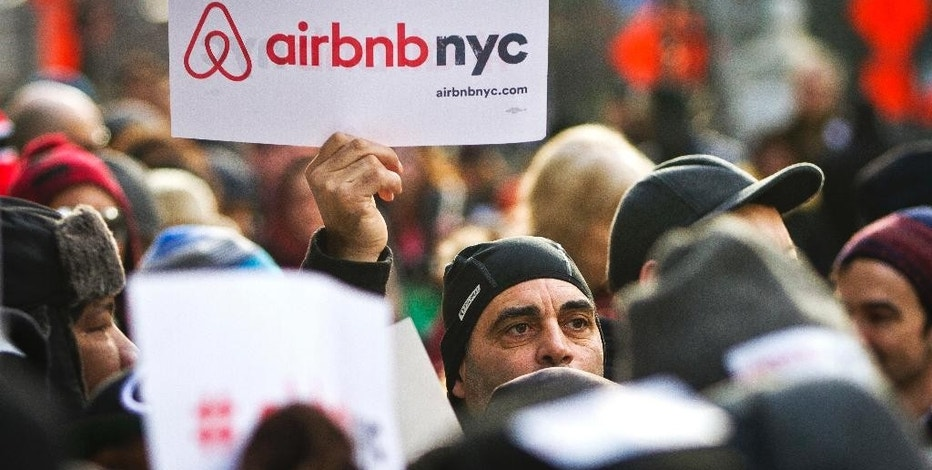 FILE - In this Jan. 20, 2015, file photo, supporters of Airbnb hold a rally outside City Hall in New York. Airbnb hosts in New York are worried about a new law that could lead to them being fined up to $7,500 for renting out their apartments. People who occasionally rent their living spaces for side income say they are getting unfairly swept up in a law aimed mostly at commercial operators. Airbnb has filed a lawsuit to block the law. (AP Photo/Bebeto Matthews, File)