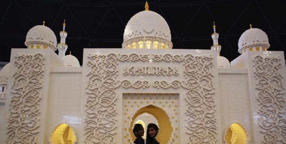 Two visitors peer through a replica of Abu Dhabi's Sheikh Zayed Grand Mosque  that is made from lego pieces, at Legoland Dubai, United Arab Emirates, on Monday, Oct. 31, 2016. The Legoland park, part of the larger Dubai Parks & Resorts project, is the first among its planned attractions to open and represents the sheikdom's efforts to expand into its southern deserts. (AP Photo/Jon Gambrell)