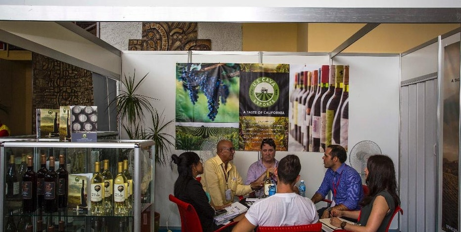 """People sit at a booth of the United States with wines from California at the 34th Trade Fair in Havana, Cuba, Monday, Oct. 31, 2016. """"The Cuban government is using the interest by U.S. companies as bait to entice the interest of companies in other countries,"""" said John Kavulich of the U.S.-Cuba Trade and Economic Council, a private group that produces mostly skeptical analyses of the prospects of U.S.-Cuba trade. """"The Cuban government is saying 'let's not give any more than absolutely necessary to U.S. companies so that the companies will continue to salivate toward illusory potential opportunities. There's far more inspiration and aspiration than reality."""" (AP Photo/Desmond Boylan)"""