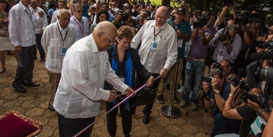 Cuba's Minister of Foreign Trade Rodrigo Malmierca, right, watches as Vice President of Cuba's Council of Ministers Ricardo Cabrisas Ruiz, left, cuts the ribbon at the opening of the 34th Trade Fair in Havana, Cuba, Monday, Oct. 31, 2016. A week-long event of commerce is under way with participants from 75 countries. Even though this is the country's largest general-interest trade fair, the Cuban government maintains a monopoly on importing and exporting and on virtually all sales of products inside the country, making the state bureaucracy the final arbiter of what business gets done. (AP Photo/Desmond Boylan)