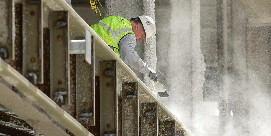 In this Thursday, May 19, 2016, photo, a worker removes dust while working on a high-rise building in Boston. On Tuesday, Nov. 1, 2016, the Commerce Department reports on construction spending for September. (AP Photo/Steven Senne)
