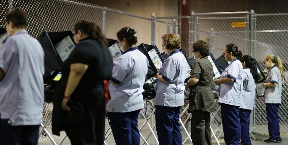 In this Oct. 26, 2016, photo, casino workers vote at an early voting site in Las Vegas.  With Election Day approaching, many small businesses want to make it easy for staffers to vote. So they're giving them flex time, balloting breaks or are opening several hours late. (AP Photo/John Locher)