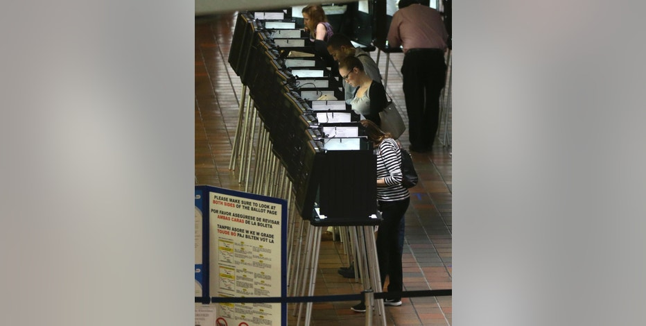 FILE - In this Oct. 24, 2016 file photo, people vote at a polling station on the first day of early voting in Miami-Dade County for the general election in Miami.  With Election Day approaching, many small businesses want to make it easy for staffers to vote. So they're giving them flex time, balloting breaks or are opening several hours late.  (AP Photo/Lynne Sladky)