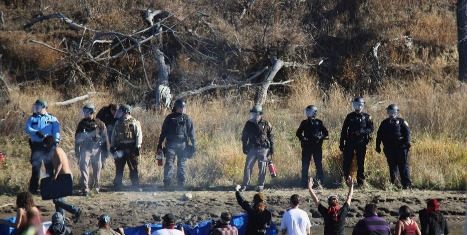 Dozens of protestors demonstrating against the expansion of the Dakota Access Pipeline wade in cold creek waters confronting local police, as remnants of pepper spray waft over the crowd near Cannon Ball, N.D., Wednesday, Nov. 2, 2016. Officers in riot gear clashed again Wednesday with protesters near the Dakota Access pipeline, hitting several dozen with pepper spray as they waded through waist-deep water in an attempt to reach property owned by the pipeline's developer. (AP Photo/John L. Mone)