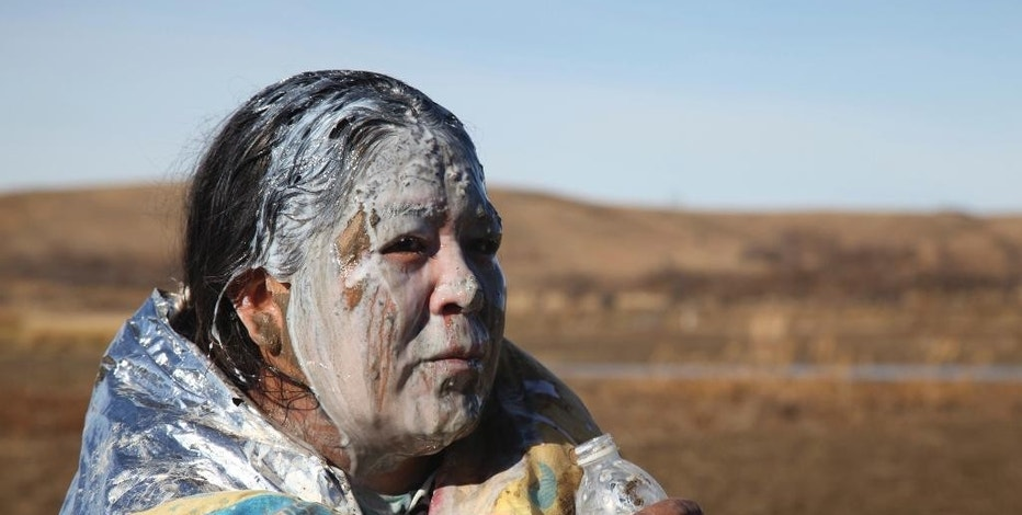 Tonya Stands recovers after being pepper sprayed by police after swimming across a creek with other protesters hoping to build a new camp to block construction of the Dakota Access Pipeline, near Cannon Ball, N.D., Wednesday, Nov. 2, 2016. Officers in riot gear clashed again Wednesday with protesters near the Dakota Access pipeline, hitting several dozen with pepper spray as they waded through waist-deep water in an attempt to reach property owned by the pipeline's developer. (AP Photo/John L. Mone)
