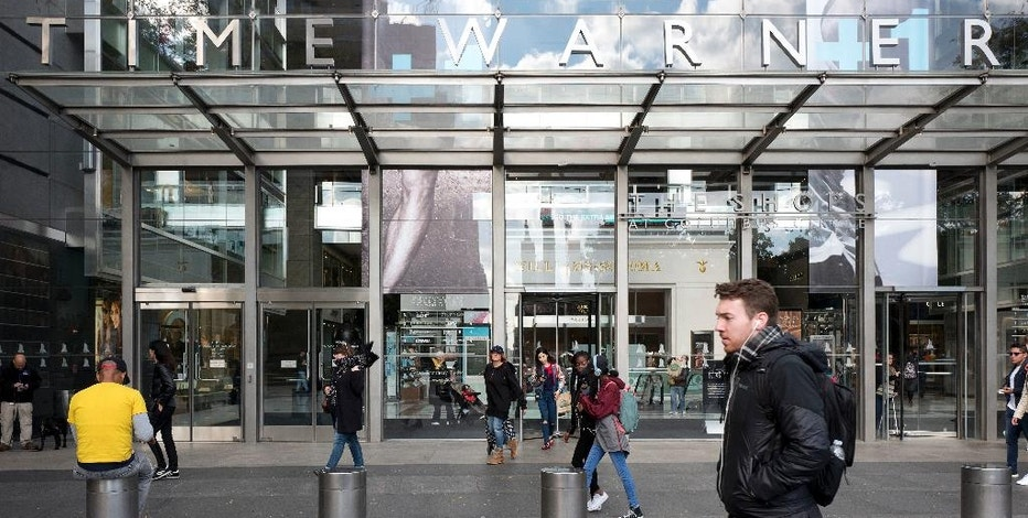 FILE - In this Monday, Oct. 24, 2016, file photo, people walk past the Time Warner building, in New York. Time Warner reports financial results Wednesday, Nov. 2, 2016. (AP Photo/Mark Lennihan, File)