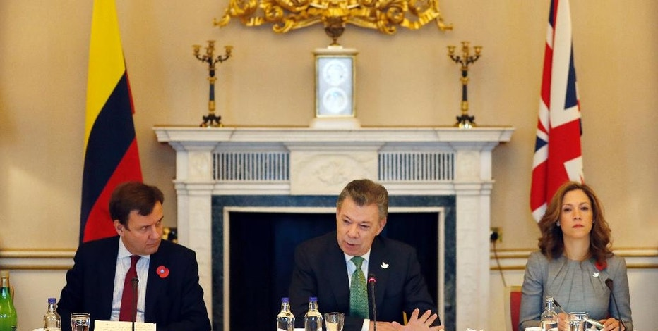 Colombia's President Juan Manuel Santos, center, sits with Greg Hands, Britain's Minister of State for Trade and Investment, left, and Maria Claudia Lacouture, Minister of Trade Industry and Tourism, right, during a business meeting at Buckingham Palace in London, Wednesday, Nov. 2, 2016. This year's Nobel Peace Prize laureate the President of Colombia Juan Manuel Santos and his wife Maria Clemencia Rodriguez are on a three day state visit to Britain. (AP Photo/Kirsty Wigglesworth, pool)