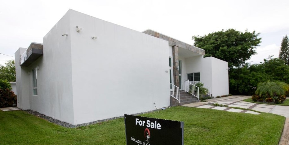 FILE - In this Tuesday, Sept. 13, 2016, file photo, a home is listed for sale in Surfside, Fla. On Thursday, Nov. 3, 2016, Freddie Mac reports on the week's average U.S. mortgage rates. (AP Photo/Wilfredo Lee, File)