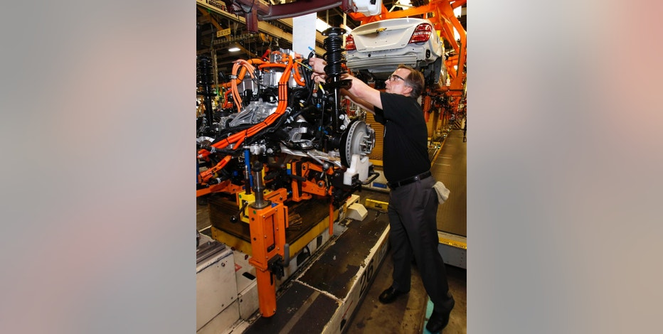 Yves Dontigny, plant launch manager at the General Motors Orion Assembly plant, points out a feature on the drive train before its installation into the Chevrolet Bolt EV, Friday, Nov. 4, 2016, in Orion Township, Mich. The Chevrolet Bolt can go more than 200 miles on battery power and will cost less than the average new vehicle in the U.S. But it's unclear whether the car can do much to shift America from gasoline to electricity in an era of $2 prices at the pump. (AP Photo/Duane Burleson)
