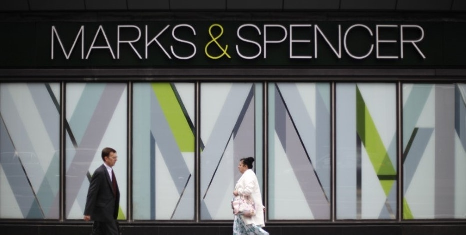 Pedestrians walk past a branch of Marks & Spencer in northwest London, Britain July 8, 2014. REUTERS/Suzanne Plunkett/File Photo