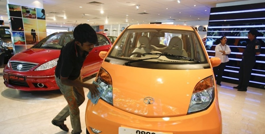 A showroom attendant cleans a Tata Nano car at their flagship showroom in Mumbai May 28, 2013. REUTERS/Vivek Prakash