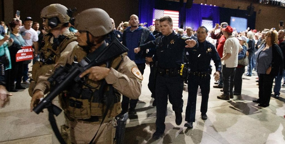 A man, at background center with blue sweater, is escorted by law enforcement officers moments after Republican presidential candidate Donald Trump was rushed offstage by Secret Service agents during a campaign rally in Reno, Nev., on Saturday, Nov. 5, 2016. (AP Photo/Evan Vucci)