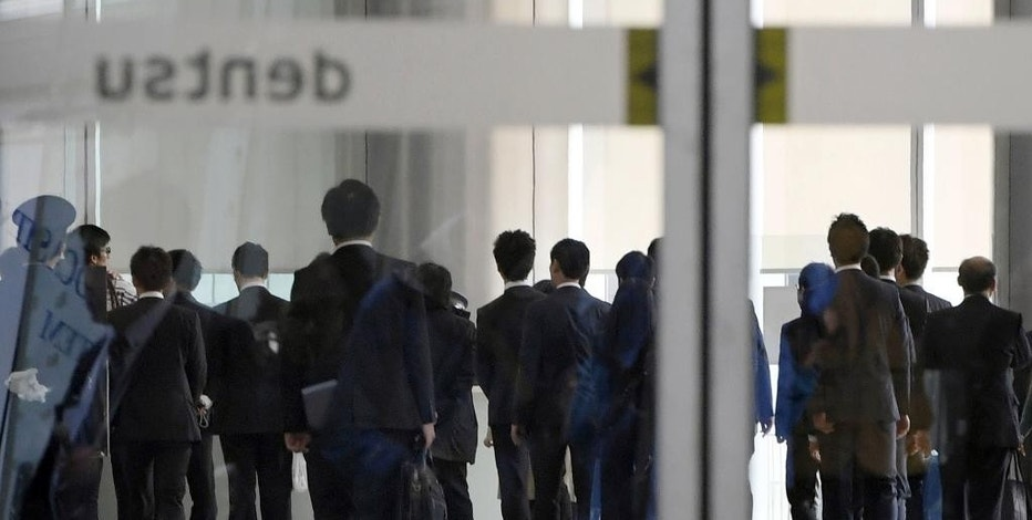"Investigators from the Health, Labor and Welfare Ministry enter the headquarters of Japan's top advertising agency Dentsu in Tokyo Monday, Nov. 7, 2016. Japanese authorities raided Dentsu Monday to conduct criminal investigation over a 24-year-old employee's suicide recognized as a result of overwork. The criminal investigation follows government recognition late September of Matsuri Takahashi's suicide as ""karoshi"" or death from overwork. (Nozomu Endo/Kyodo News via AP)"