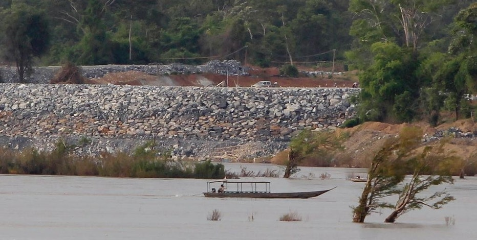 FILE - In this June 20, 2016 file photo, a fishing boat passes near a construction site of the Don Sahong dam, near Cambodia-Laos borders, in Preah Romkel village, Stung Treng province, northeast of Phnom Penh, Cambodia. The Mekong River Commission, an organization that groups together Laos, Cambodia, Vietnam and Thailand for joint management of the river, said in a statement it has received notice from Laos that it will undertake a process of consultation about the Pak Beng dam. (AP Photo/Heng Sinith, File)