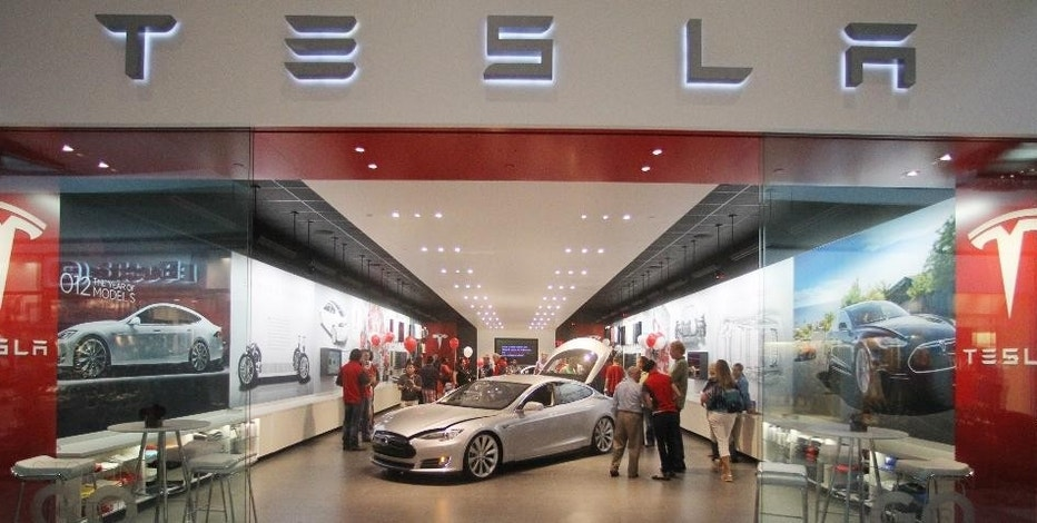 FILE - This  Friday, July 20, 2012, file photo, shows the Tesla showroom at the Washington Square Mall, in Portland, Ore. Tesla Motors said Tuesday, Nov. 8, 2016, that it has agreed to buy German engineering company Grohmann Engineering to help automate its electric car manufacturing. (AP Photo/Rick Bowmer, File)