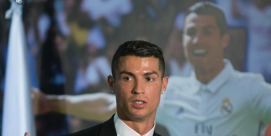 Real Madrid's Cristiano Ronaldo leaves a press conference after signing a new contract at the Santiago Bernabeu stadium in Madrid, Spain, Monday, Nov. 7, 2016. Real Madrid have extended Ronaldo's contract until June 2021, when the three-time world player of the year will be 36. Financial details were not released, although the star forward is expected to remain the team's top-paid player. (AP Photo/Paul White)
