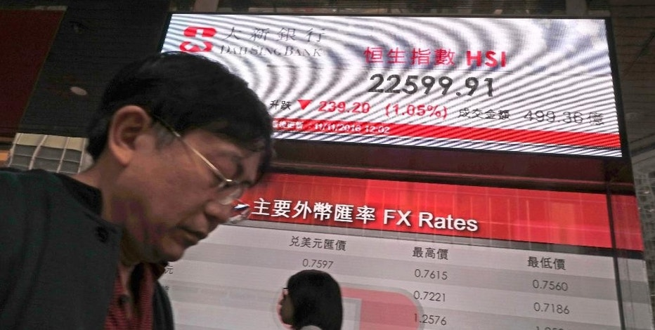 A man walks past an electronic board showing the Hong Kong stock index outside a local bank in Hong Kong, Friday, Nov. 11, 2016. Asian shares were mixed Friday and the dollar recovered, but expectations grew that President-elect Donald Trump's trade policies might fuel inflation, even as some of the initial jitters have subsided. (AP Photo/Vincent Yu)