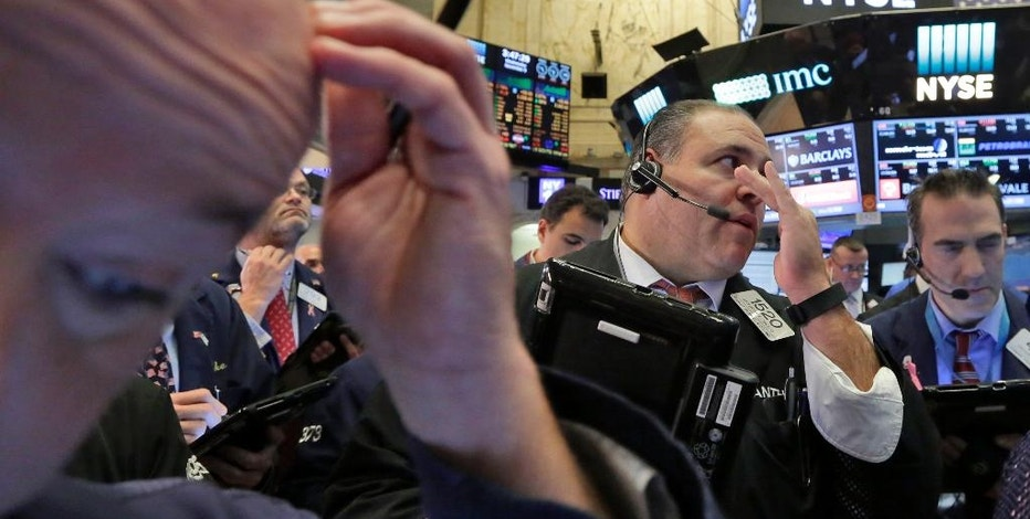 FILE - In this Wednesday, Nov. 9, 2016, file photo, Anthony Riccio, center, works with fellow traders on the floor of the New York Stock Exchange. Investors have been yanking money out of bonds around the world, sending prices tumbling and wiping out several months of gains in widely held U.S. government debt since the election. (AP Photo/Richard Drew, File)