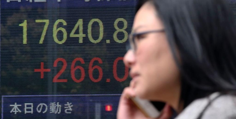 A woman walks by an electronic stock board of a securities firm in Tokyo, Monday, Nov. 14, 2016. Asian shares were mostly lower Monday but Japan's benchmark got a boost from a weaker yen. Other regional bourses have gradually steadied after a bout of turmoil following the U.S. presidential election. (AP Photo/Koji Sasahara)