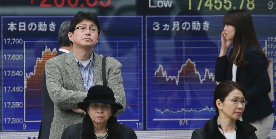 People stand in front of an electronic stock board of a securities firm in Tokyo, Monday, Nov. 14, 2016. Asian shares were mostly lower Monday but Japan's benchmark got a boost from a weaker yen. Other regional bourses have gradually steadied after a bout of turmoil following the U.S. presidential election. (AP Photo/Koji Sasahara)