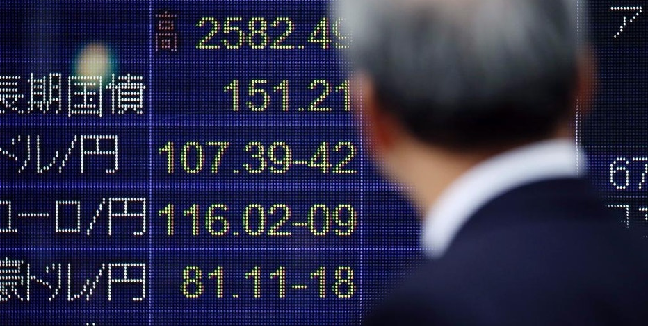 A man looks at an electronic stock board of a securities firm in Tokyo, Monday, Nov. 14, 2016. Asian shares were mostly lower Monday but Japan's benchmark got a boost from a weaker yen. Other regional bourses have gradually steadied after a bout of turmoil following the U.S. presidential election. (AP Photo/Koji Sasahara)