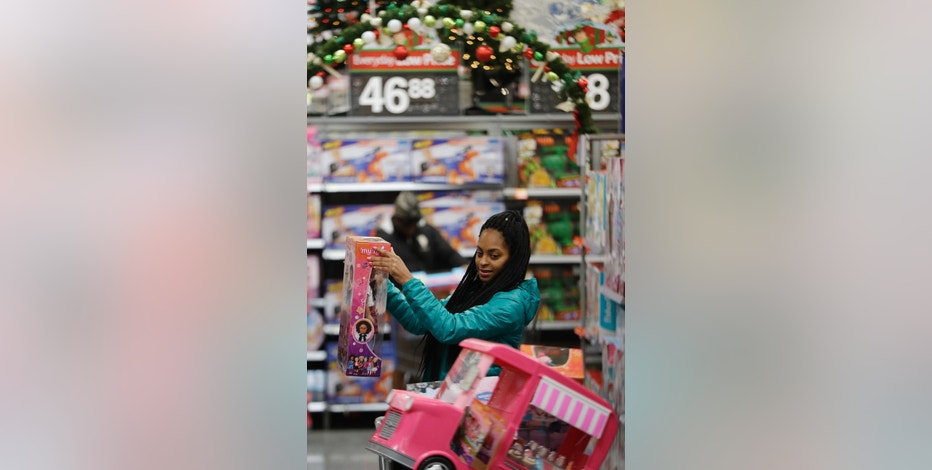 FILE - In this Wednesday, Oct. 26, 2016, file photo, Choisette Hargon, of Paterson, N.J., shops for toys ahead of Christmas at Wal-Mart in Teterboro, N.J. It's easy to get caught up in the excitement of holiday shopping, but it's not always as easy to foot the bill. The National Retail Federation says consumers plan to spend an average of $935.58 during the holiday shopping season, which is the second highest level on record. (AP Photo/Julio Cortez, File)