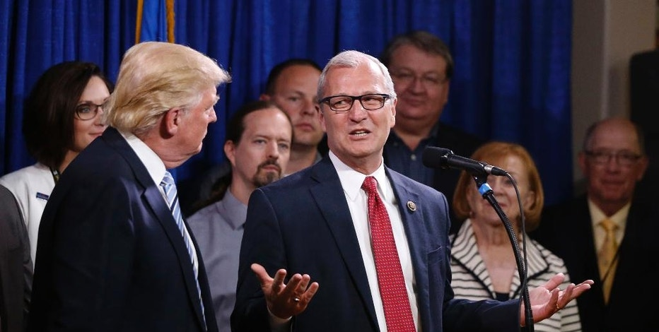 FILE - In this May 26, 2016 file photo, Rep., Kevin Cramer, R-ND, right, talks about being one of the first to endorse Republican presidential candidate Donald Trump, as Trump meets with some of the 22 delegates from North Dakota to the Republican National Convention in Bismarck, N.D.  Cramer is being considered to run Trump's Energy Department, according to transition planning documents obtained by The Associated Press.  (AP Photo/Charles Rex Arbogast)