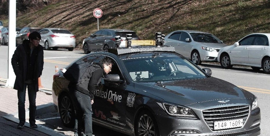A man looks inside the driverless car called Snuber during a driving demonstration at the Seoul National University's campus in Seoul, South Korea, Tuesday, Nov. 15, 2016. Seoul National University professor Seo Seung-woo said that a self-driving car developed by his team will start roaming Seoul streets early next year thanks to a revised law that took effect Tuesday. (AP Photo/Ahn Young-joon)