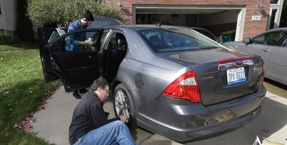 In a photo from Oct. 22, 2016 in Saline, Mich., Associated Press Auto Writer Tom Krisher cleans a wheel on a 2010 Ford Fusion that was purchased by Casey Smith, rear, after an extensive search for a used car. When shopping for a low-priced used car, three things will become evident: Some people want to swindle you. Few take proper care of their cars and the search will take a long time. (AP Photo/Carlos Osorio)