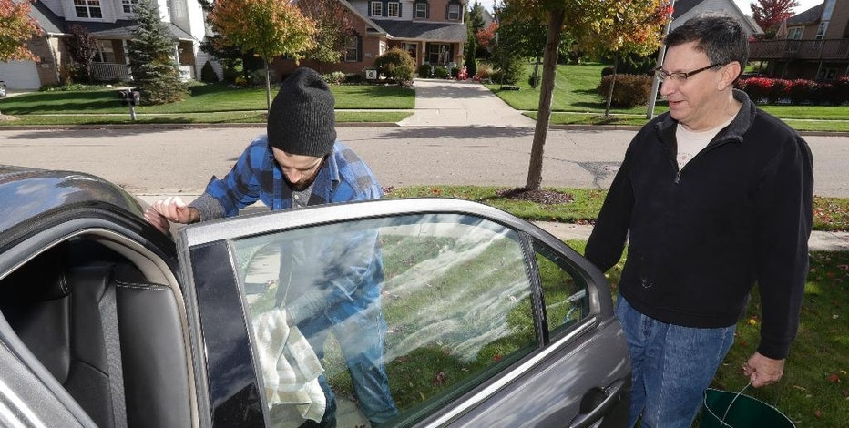 In a photo from Oct. 22, 2016 in Saline, Mich., Associated Press Auto Writer Tom Krisher, right, and Casey Smith, left, clean a 2010 Ford Fusion that was purchased by Smith after an extensive search for a used car. When shopping for a low-priced used car, three things will become evident: Some people want to swindle you. Few take proper care of their cars and the search will take a long time. (AP Photo/Carlos Osorio)