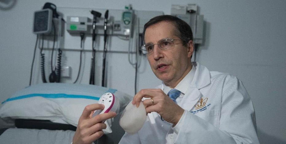 In this Thursday, Oct. 20, 2016, photo, Dr. Jeffrey Ascherman, chief of the Division of Plastic Surgery and professor of surgery at NewYork-Presbyterian/Columbia University Medical Center, holds an AeroForm kit during an interview in New York. Doctors are testing the device that would let women contribute to the breast reconstruction process at home. It is aimed at not only making treatment more comfortable and convenient, but also giving women a sense of control _ something cancer often takes away. (AP Photo/Mary Altaffer)