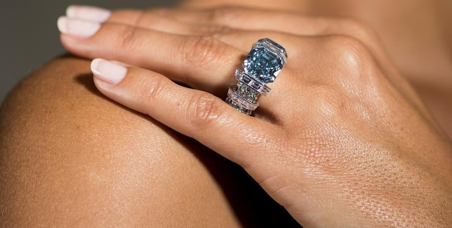 "FILE - In this file photo dated Wednesday Nov. 9, 2016, a model displays the ""Sky Blue Diamond"" ring, a fancy vivid blue 8.01 carat jewel of imperial Russian heritage during a Sotheby's press preview in Geneva, Switzerland.  The diamond ring is the centerpiece of its latest Geneva jewelry auction on Wednesday Nov. 16. (Jean-Christophe Bott/Keystone File via AP)"