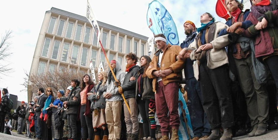 Dakota Pipeline protesters stand arm-in-arm at the intersection of Rosser Avenue and Fourth Street in downtown Bismarck, N.D., after marching from the state Capitol to the William L. Guy Federal Building, Monday, Nov. 14, 2016. (Mike McCleary/The Bismarck Tribune via AP)