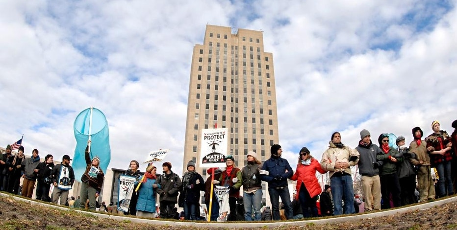 Dakota Pipeline protesters stand arm-in-arm in front of the state Capitol in Bismarck, N.D., before marching downtown to the William L. Guy Federal Building, Monday, Nov. 14, 2016. (Mike McCleary/The Bismarck Tribune via AP)