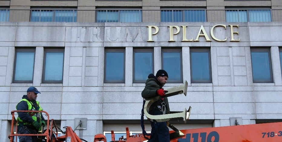 Workmen remove the letters off a building formerly known as Trump Place in New York, Wednesday, Nov. 16, 2016. Donald Trump's name is being stripped off three luxury apartment buildings after hundreds of tenants signed a petition saying they were embarrassed to live in a place associated with the Republican president-elect. (AP Photo/Seth Wenig)