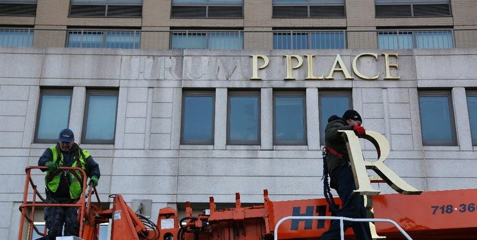 Workmen remove the letters from a building formerly known as Trump Place in New York, Wednesday, Nov. 16, 2016. Donald Trump's name is being stripped off three luxury apartment buildings after hundreds of tenants signed a petition saying they were embarrassed to live in a place associated with the Republican President-elect. (AP Photo/Seth Wenig)