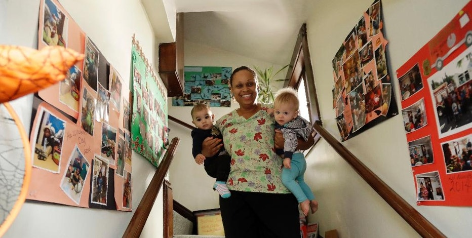 In this Thursday, Oct. 20, 2016, photo, Nancy Harvey, owner of Lil' Nancy's Primary Schoolhouse, carries two toddlers at her home which has she has converted into a child care center, in Oakland, Calif.  Most U.S. households are heading for a worse lifestyle in retirement than they had while they were working, because they simply aren't saving enough, experts say. Harvey, who has less than $2,000 saved despite her decades of work, plans to continue with real-estate classes in hopes that it can provide a second job.(AP Photo/Marcio Jose Sanchez)